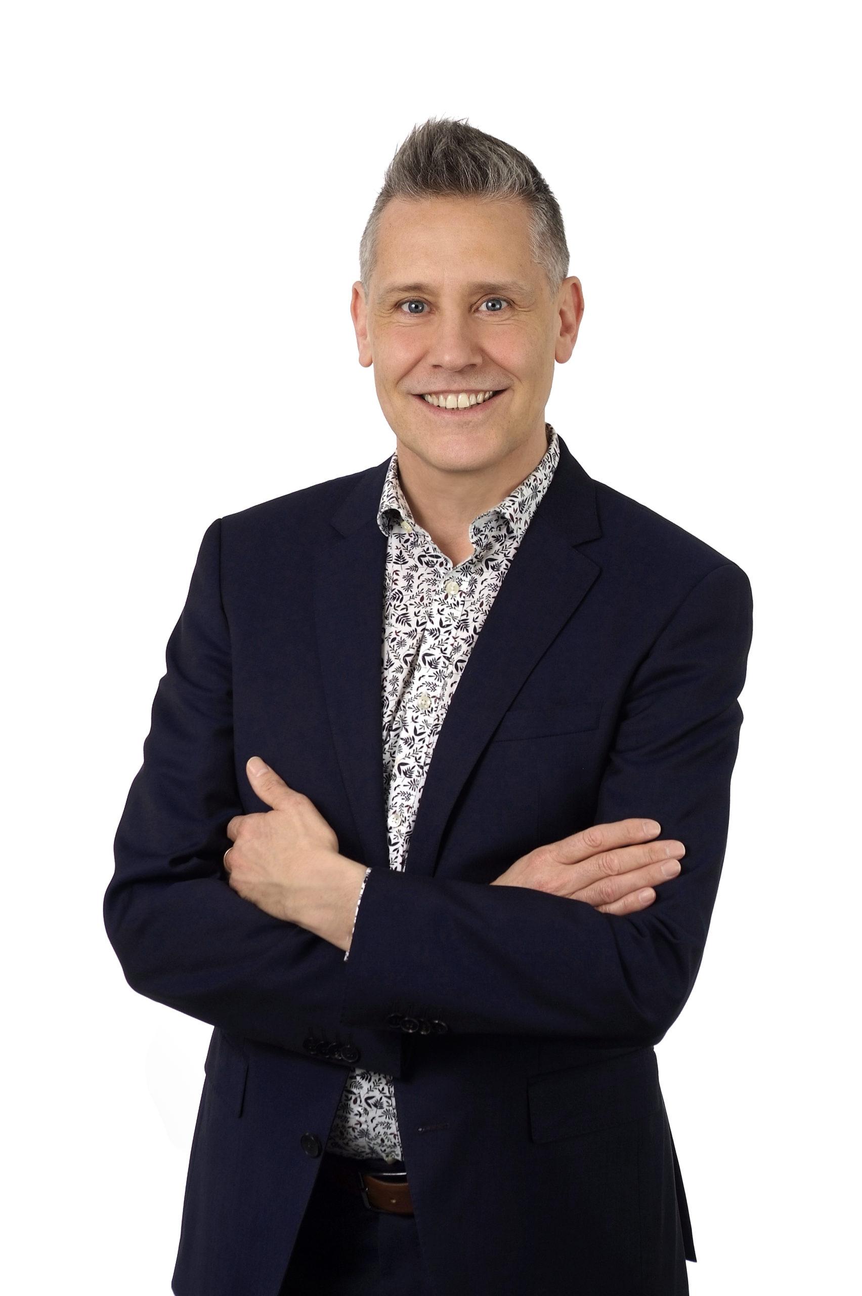 Stefan Burkhardt steht lächelnd neben den nachfolgenden Themen
