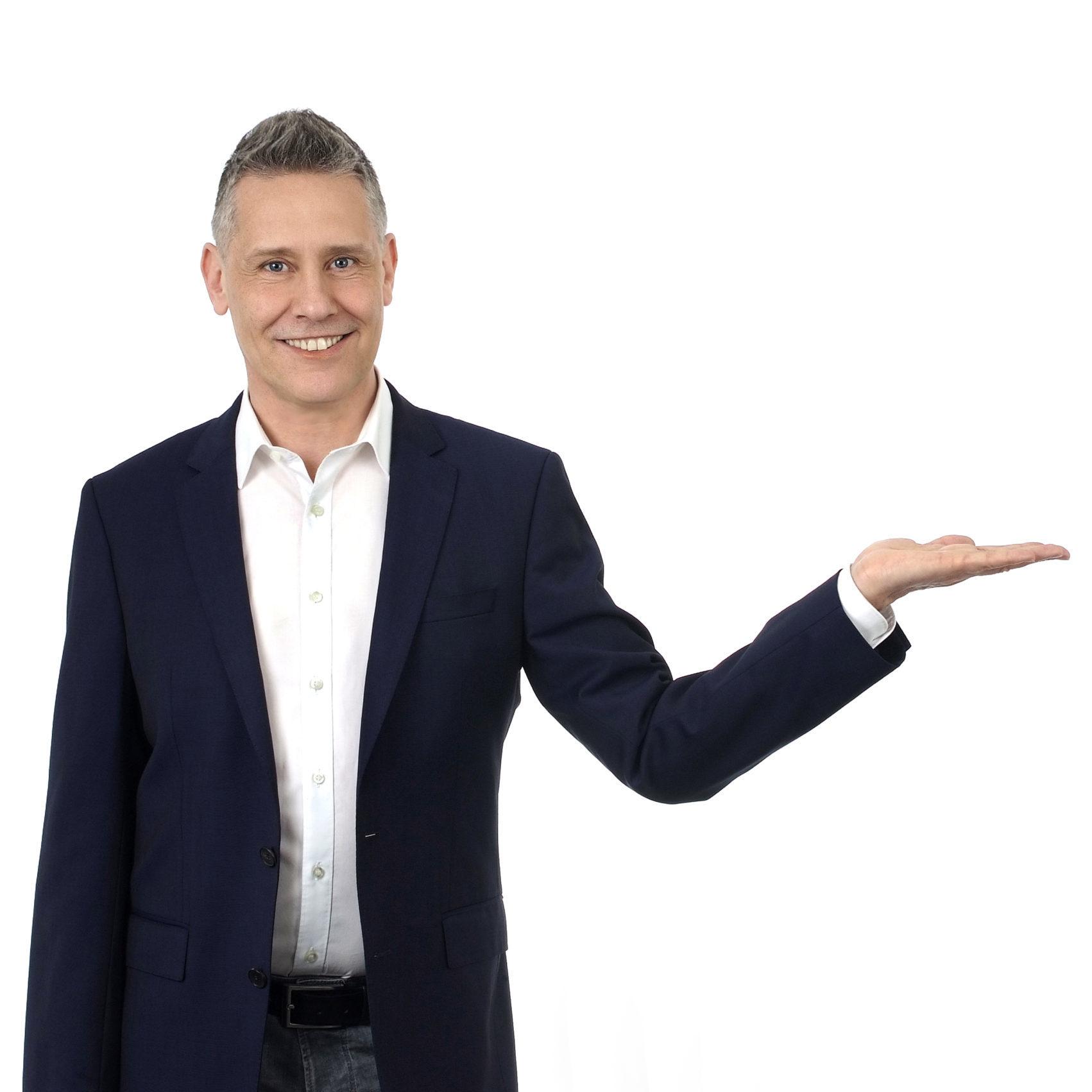 Stefan Burkhardt zeigt lächelnd auf ein Kontaktformular