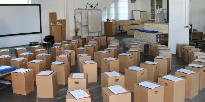 Papphocker sind als Sitzmöbel in Halbkreisen um eine Leinwand aufgestellt. Darauf liegt jeweils ein Klemmbrett mit Teilnehmerunterlagen.