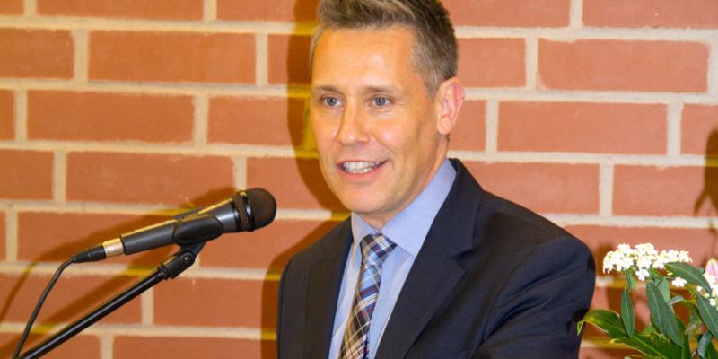 Stefan Burkhardt spricht in ein Mikrofon an einem Rednerpult.